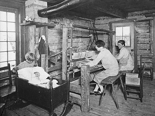 A mother shown weaving beside her children. Cap-à-l'Aigle, QC. Library and Archives Canada, PA-040744